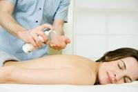 mujer tumbada en una camilla dándose un masaje